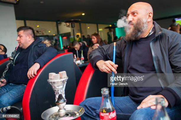 KHAN a 50yearold former football hooligan turned teacher watches Chelsea v Tottenham Hotspur on TV in a Shisha lounge in his home town of Leicester...