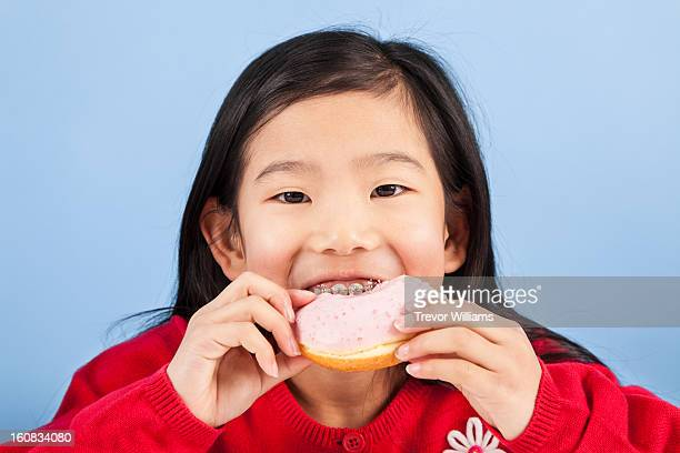 a 9 year old girl biting into a doughnut
