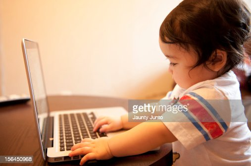 a baby boy playing with a laptop : Stock Photo