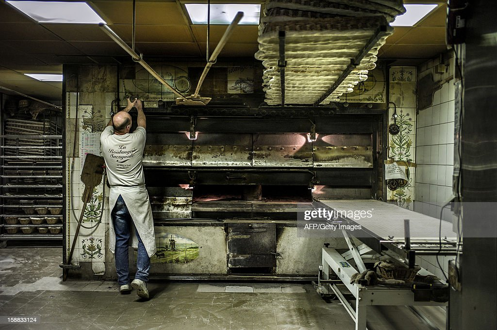 a baker prepares the bread oven, on December 27, 2012 in a bakery of Ecole en Bauges, French Alps.