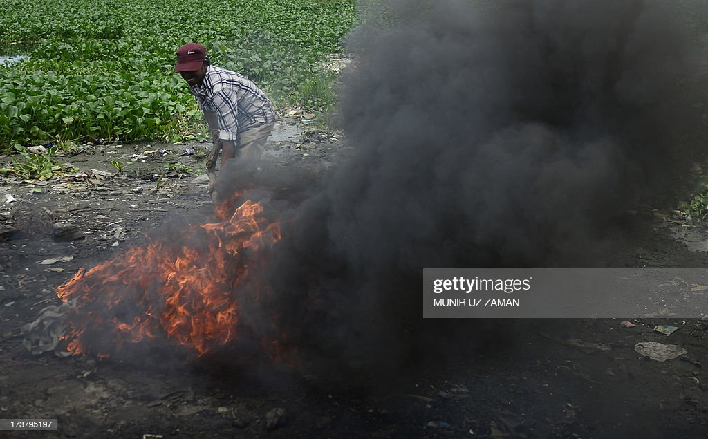 a Bangladeshi labourer burns cables to extract wire during an ongoing nationwide strike called by the Bangladesh Jumaat-e-Islami in Dhaka on July 18, 2013. The strike has been called to protest the death sentence of the party's secretary general Ali Ahsan Mohammed Mujahid. A Bangladesh court has sentenced a leading Islamist politician to death for war crimes including murder, torture and kidnapping, as religious hardliners imposed a nationwide strike over the verdict. Ali Ahsan Mohammad Mujahid, 65, the second-highest ranked official of the country's largest Islamic party, was found guilty of five of seven charges by the much-criticised International Crimes Tribunal. AFP PHOTO/Munir uz ZAMAN
