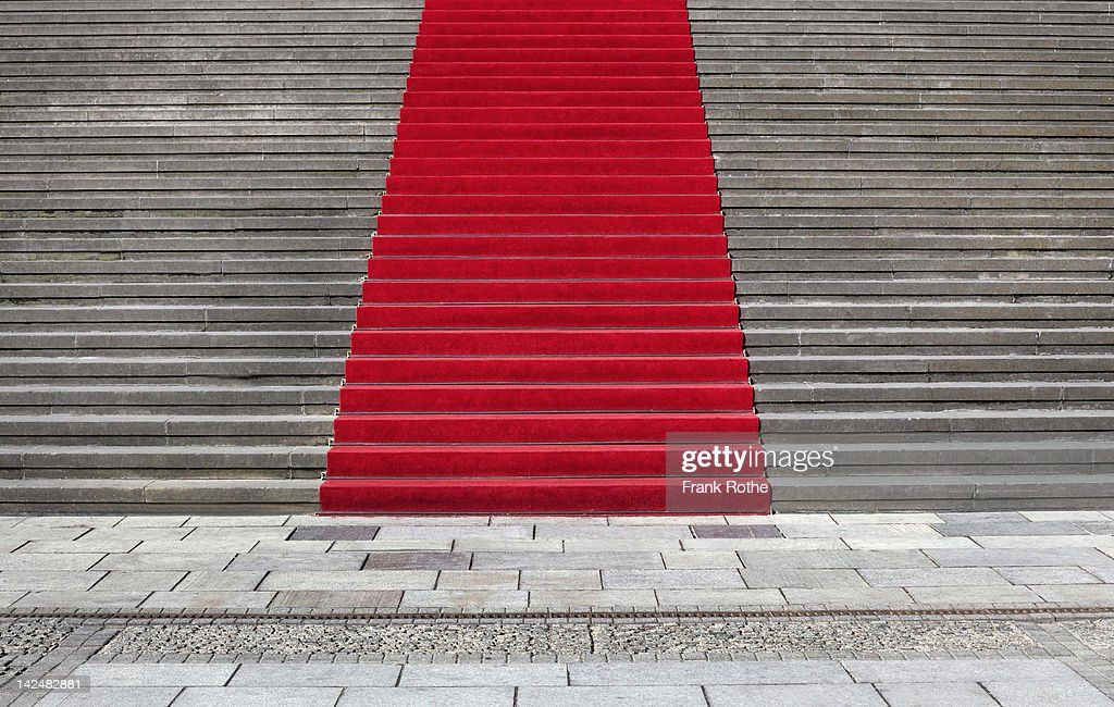a beautiful red carpet leads up a great staircase : Stock Photo