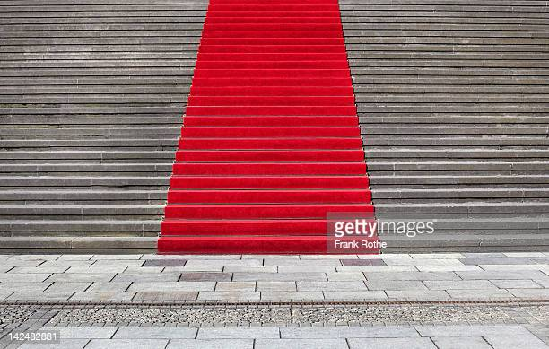 a beautiful red carpet leads up a great staircase