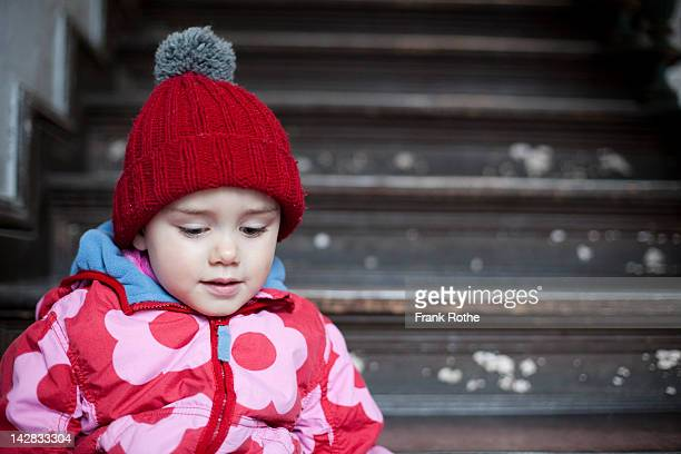 a beautiful young kid with a bobble hat at stairs