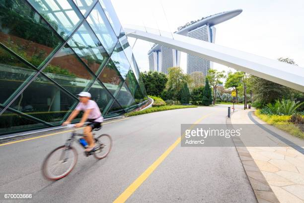 a bicycle riding along botanic garden in a modern city with marina bay sands in background