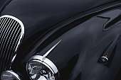 a black jaguar sports car hood showing a grill and headlight