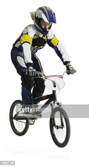 a blond caucasian teenage girl wearing a bike racing suit and helmet is airborne on her dirtbike