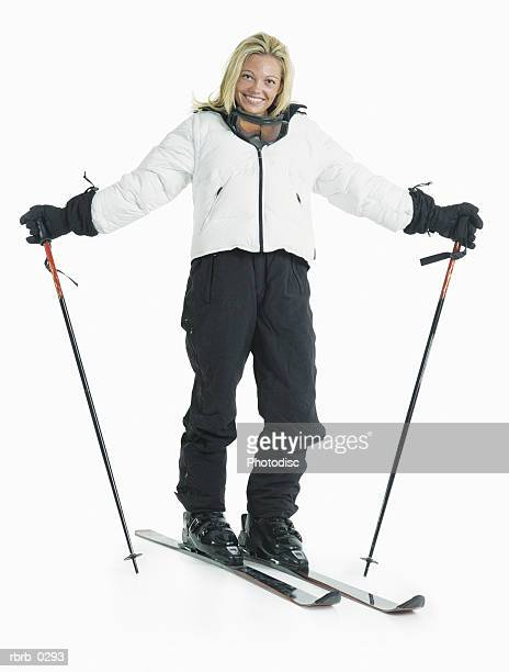 a blond female caucasian skier is wearing a white jacket and black ski pants as she stands on her skis and holds her poles out to the side