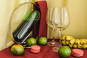 a bottle of wine glasses and fruit on the table