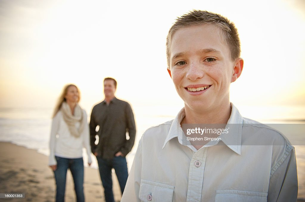 a boy at the beach, parents in background : Stock Photo