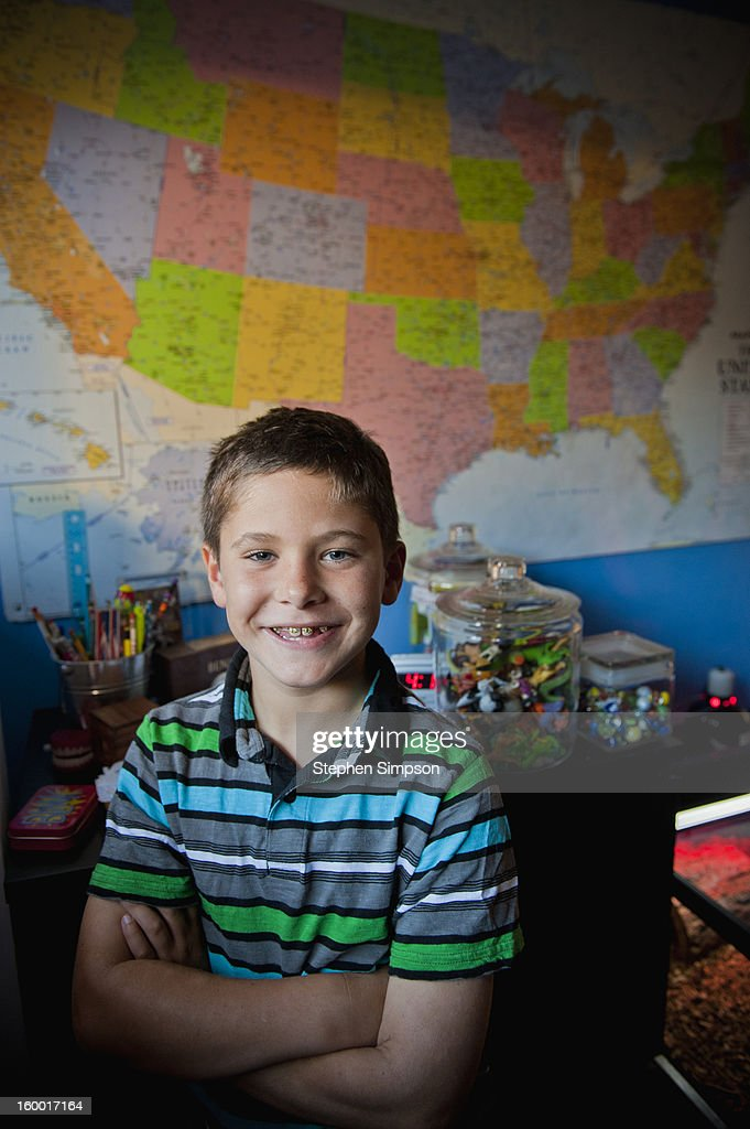 a boy in his bedroom with wall map and toys : Stock Photo