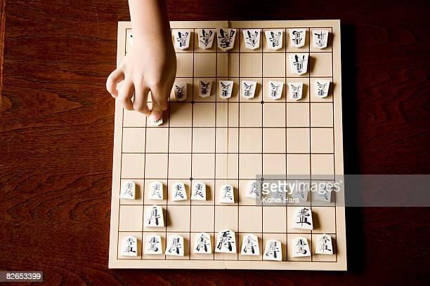a boy playing shogi game
