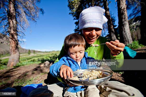 a boy sits on his mothers lap while they eat noodles in the backcountry. They are camped at Squaw Pass.