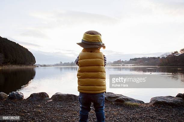 a boy standing at the lakeside