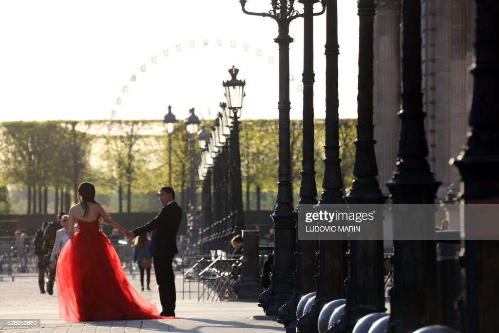 a bride dressed in a red dress with her husband walk along the Louvre pyramid for photo souvenirs at sunset, in Paris, on may 4, 2016. / AFP / LUDOVIC