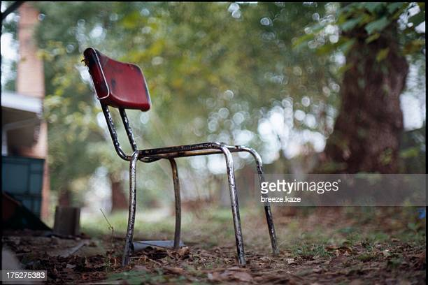 a broken chair with red back
