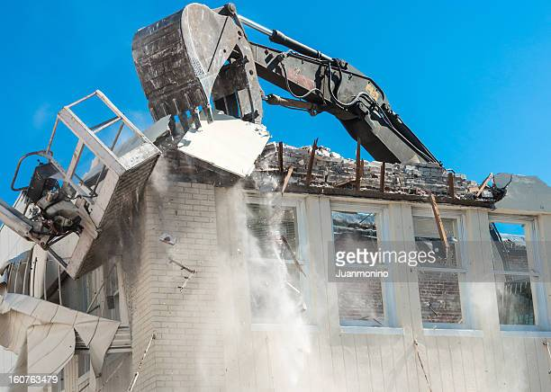 a building being demolished by a large bulldozer