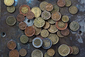 a bunch of various coins on a copper plate