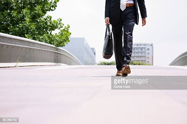 a business man walking on the road