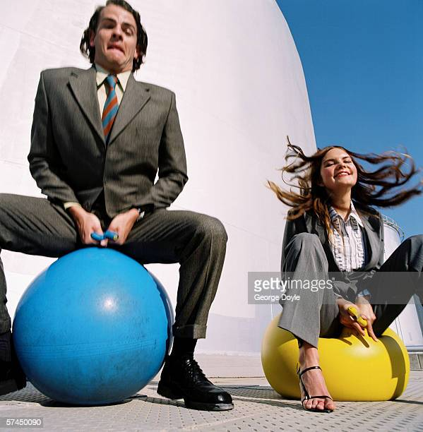 a businessman and woman bouncing on rubber balls