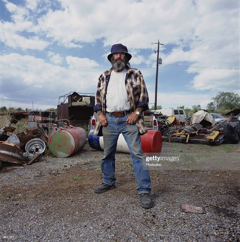a casually dressed older caucasian man with long facial hair wearing dirty jeans and a floppy hat is standing in a yard full of junk