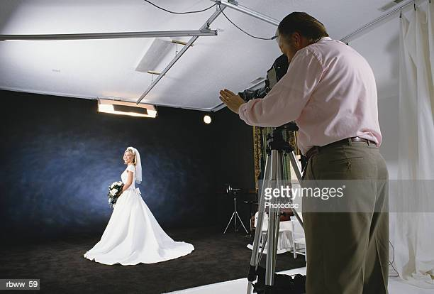 a caucasian bride poses in her bridal gown for a photographer in his studio