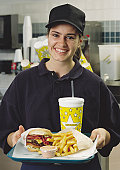 a caucasian brunette fast food employee smiles while holding a tray of food