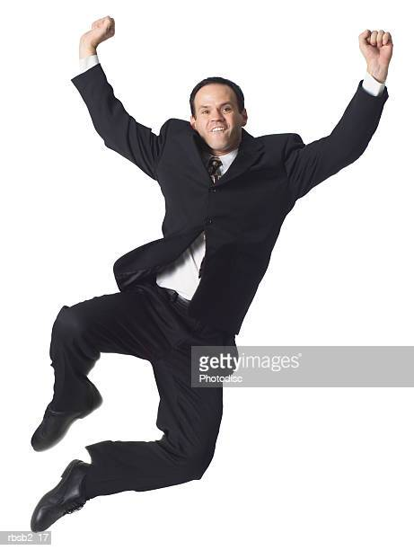 a caucasian business man in a dark suit jumps playfully up into the air