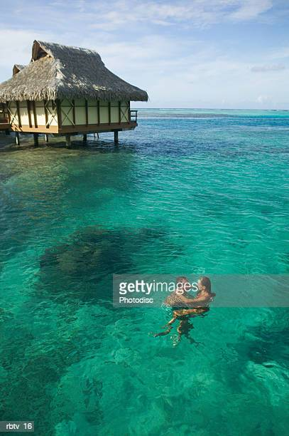 a caucasian couple embrace and swim through the clear water at a tropical resort
