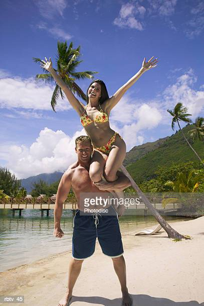 a caucasian couple play on a beach by the woman jumping up on the shoulders of the man