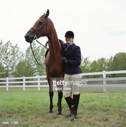 a caucasian female horseback rider stands with her horse and smiles : Stock Photo
