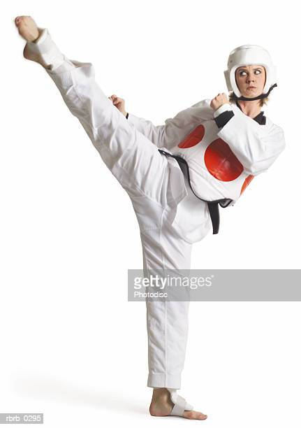 a caucasian female karate black belt dressed in white is wearing a protective vest with a red circle and kicking high to her right