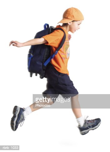 a caucasian little boy with an orange ballcap and a backpack runs along to school : Stock Photo
