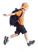 a caucasian little boy with an orange ballcap and a backpack runs along to school
