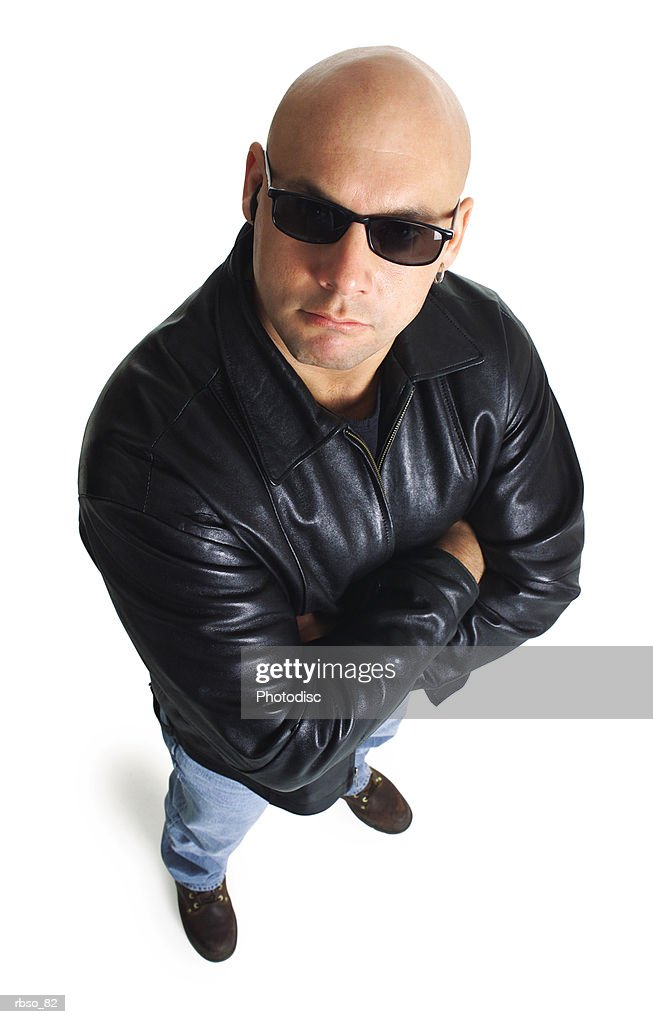 a caucasian male bodyguard in a leather jacket and sunglasses looks sternly up at the camera : Stock Photo