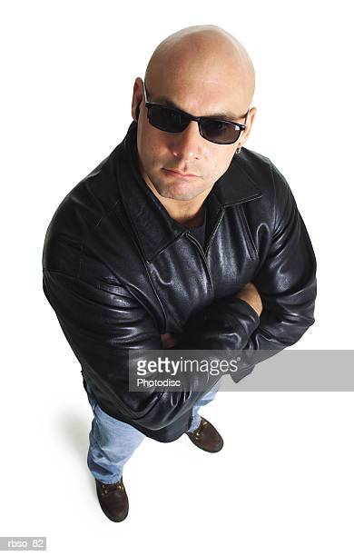 a caucasian male bodyguard in a leather jacket and sunglasses looks sternly up at the camera