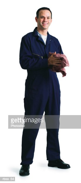 a caucasian male mechanic in a blue jumpsuit cleans his hands with an oily rag