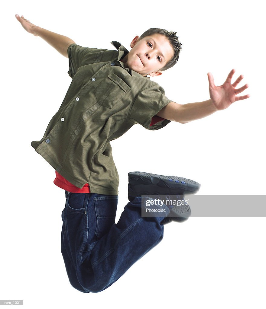 a caucasian male teen in jeans and a brown shirt jumps playfully into the air : Stock Photo