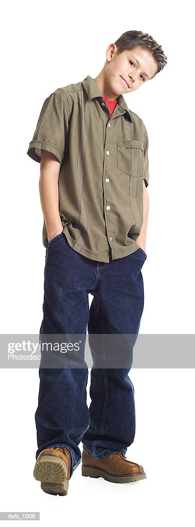 a caucasian male teen in jeans and a green shirt puts his hnads in his pockets and smirks : Stock Photo