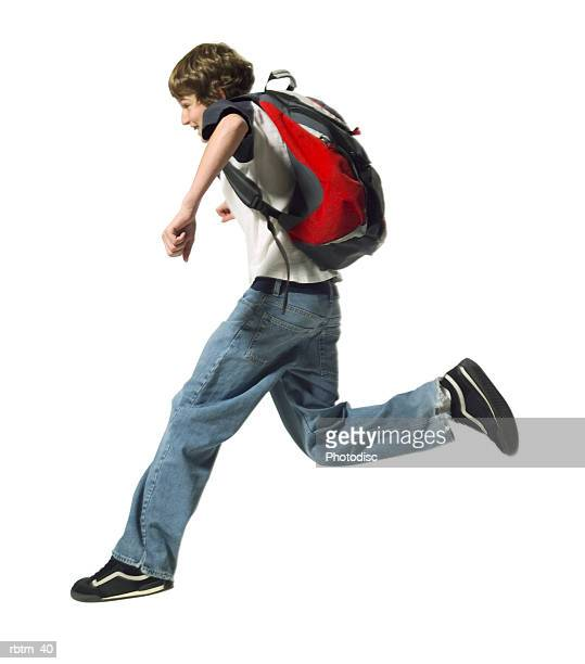 a caucasian male teen wearing a backpack runs and jumps through the air