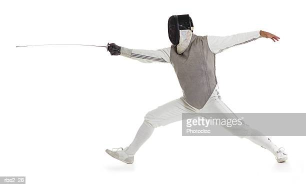 a caucasian male wearing a mask and protective gear lunges forward with his sword while fencing