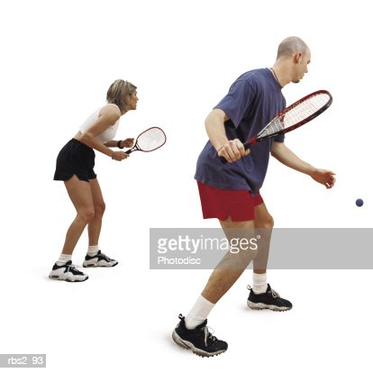a caucasian man and woman are facing towards the side as they hold rakets and play raketball