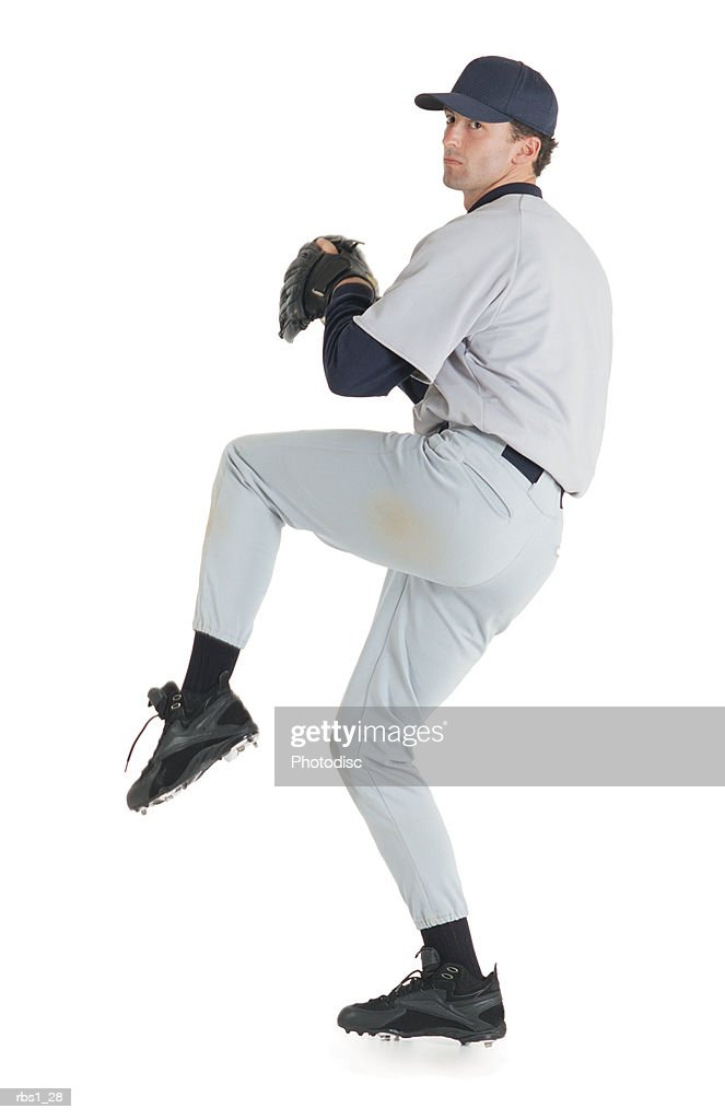 a caucasian man wearing a white baseball uniform has on a baseball hat and a glove as he stands on one let ready to throw a pitch : Stock Photo