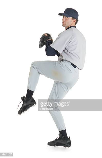 a caucasian man wearing a white baseball uniform has on a baseball hat and a glove as he stands on one let ready to throw a pitch