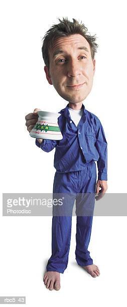 a caucasian man wearing blue pajamas holds out his mug and looks very sleepy