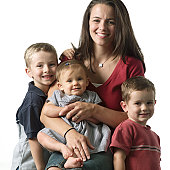 a caucasian mother smiles as she sits with her sons and new daughter