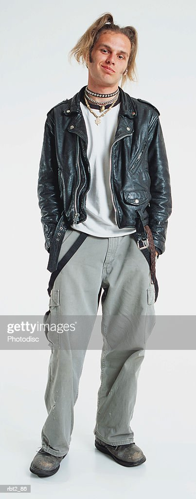 a caucasian teenage boy with ponytails and a leather jacket is standing and smirking at the camera