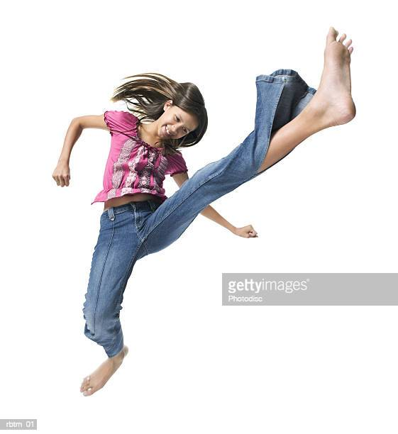 a caucasian teenage girl in jeans and pink blouse kicks and jumps wildly into the air