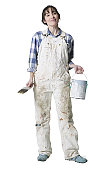 a caucasian woman dressed in overalls smiles as she holds a paint brush and paint bucket