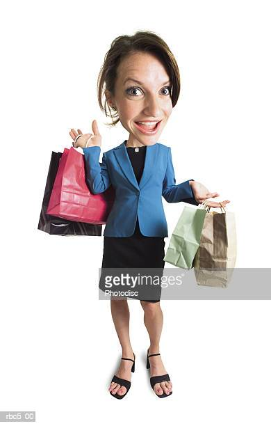 a caucasian woman holds various shopping bags and looks happily at the camera